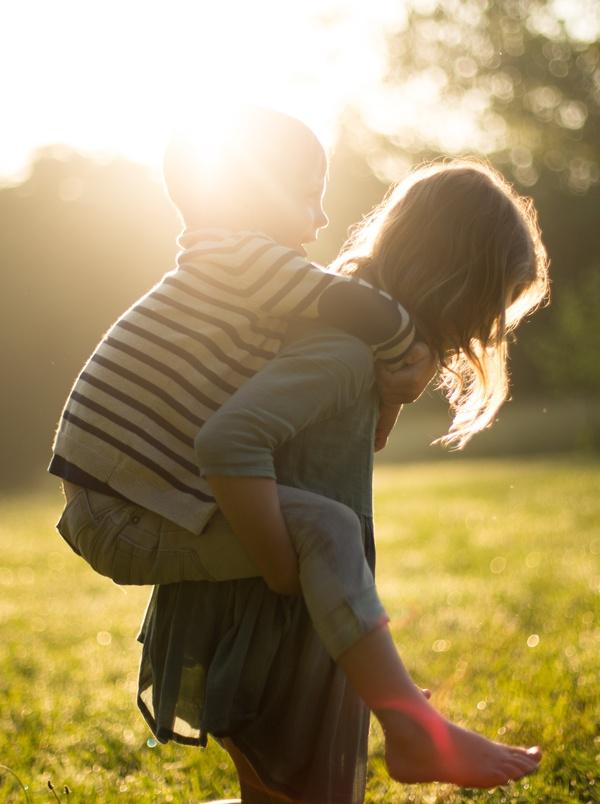 Petite fille portant son frère sur le dos, coucher de soleil