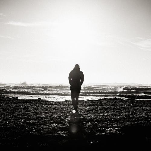homme de dos marchant vers la mer